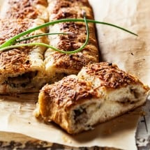 Long, thin loaf of morel bread, cut open with herbs.