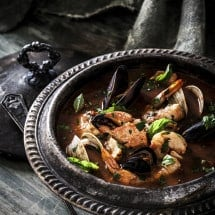 Cioppino Seafood Stew Soup in dark metal pot on gray wood surface.