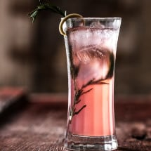 Tall glass filled with pink liquid and rosemary garnish in shadow.