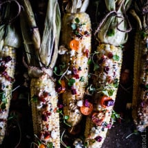 Cobs of corn with the husks pulled up colored with spices and peppers. Dark photography.