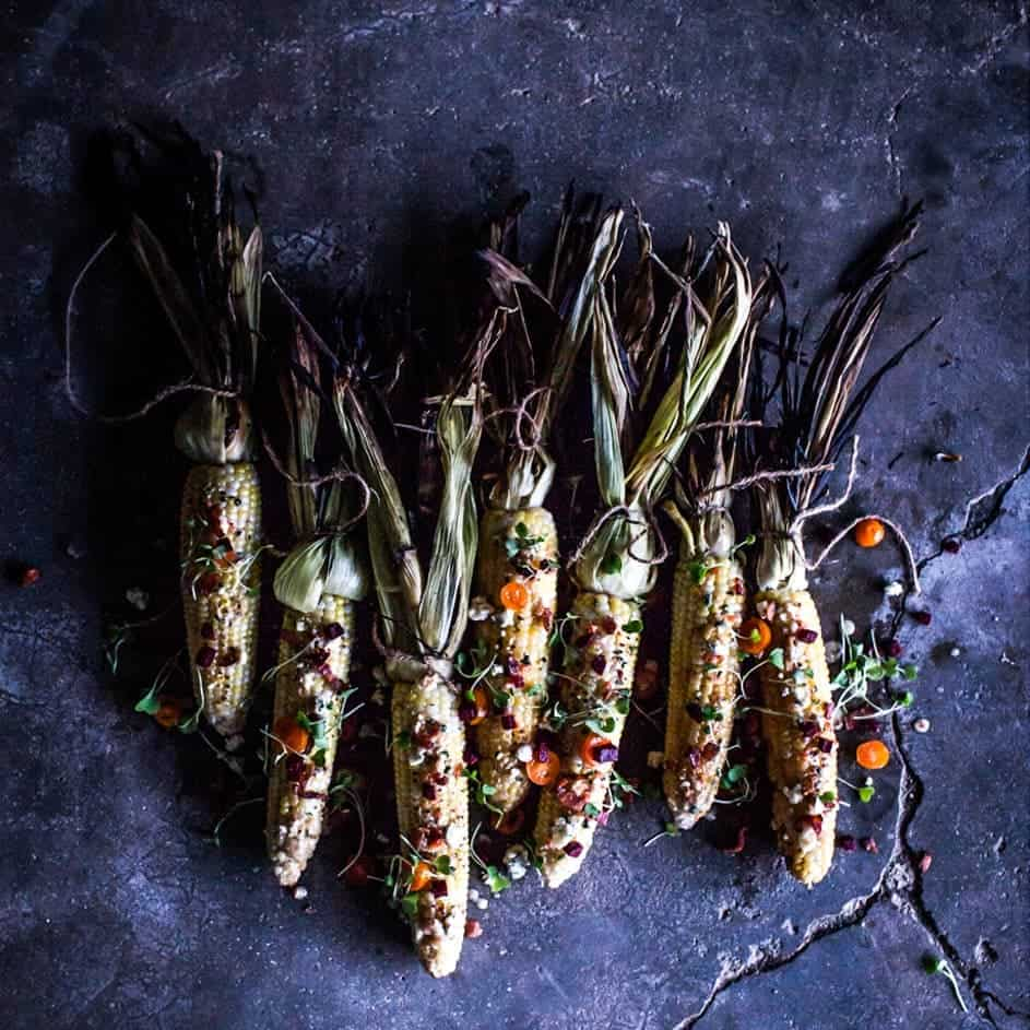 Grilled corn on the cob with vibrant spices on a moody surface