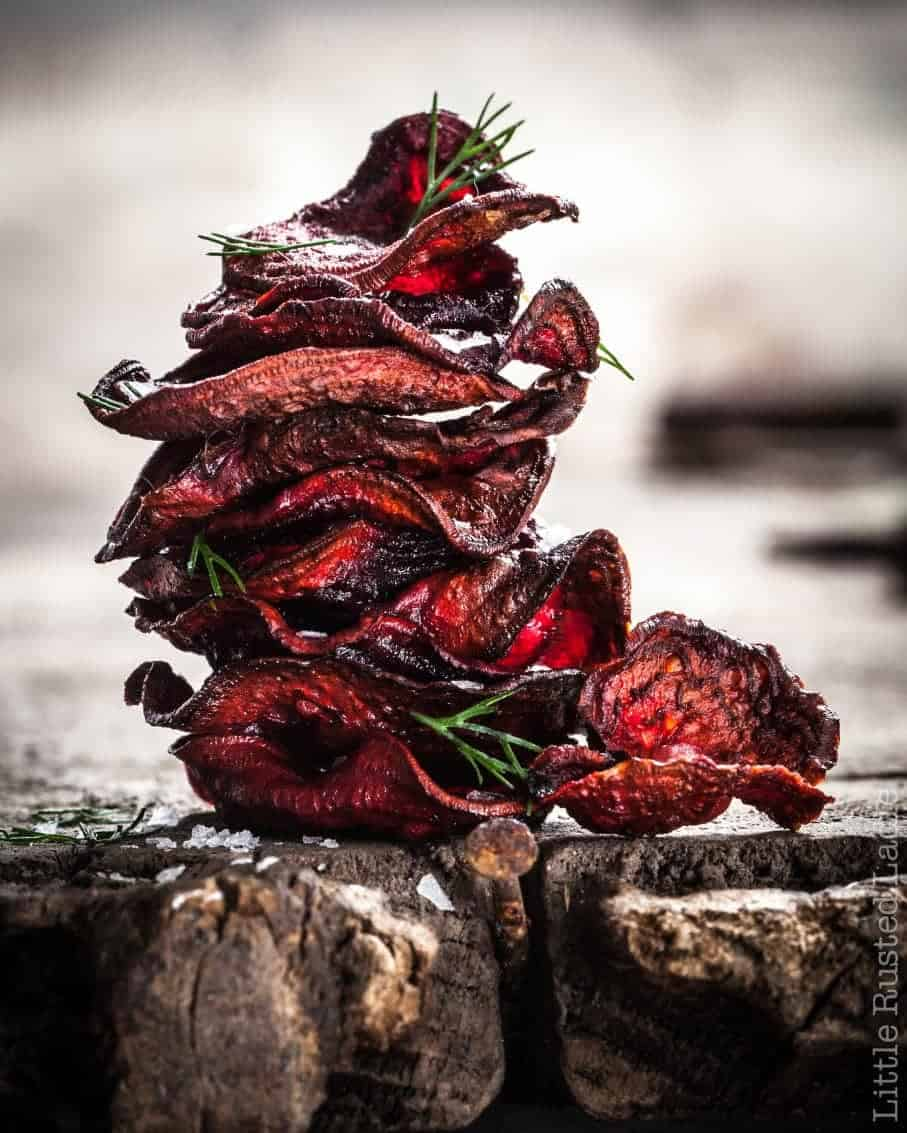 A stack of baked red beet chips with herbs.