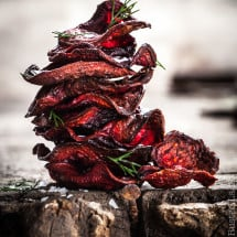 a stack of red beet chips on a wooden surfacce