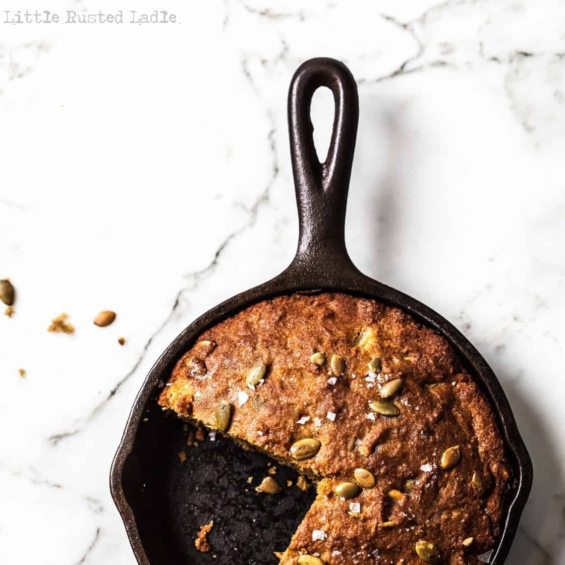 cast iron pumpkin bread on bright marble surface