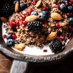 Closeup of rustic bowl containing fresh fruit, milk, nuts, and quinoa