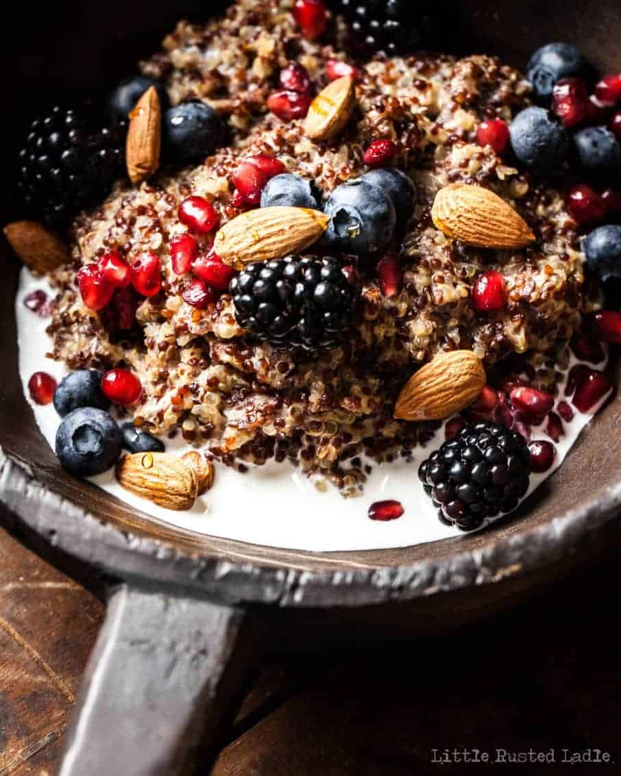 Closeup of rustic bowl containing fresh fruit, milk, nuts, and quinoa for healthy oatmeal
