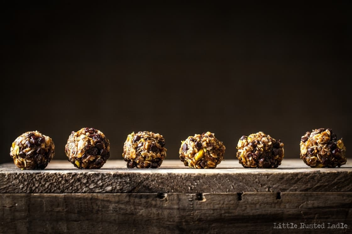 A line of textured healthy granola bites on a rustic wood surface.