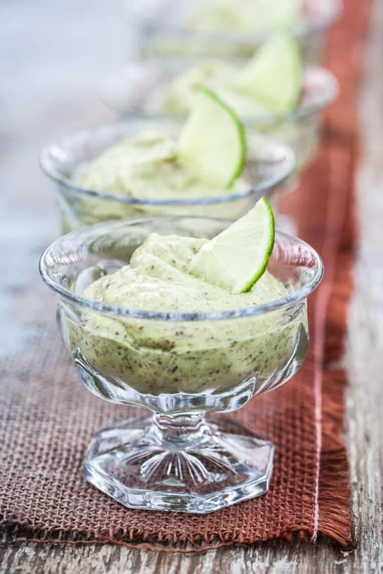 A receding line of crystal ice cream dishes filled with light green key lime pudding on rustic table runner.