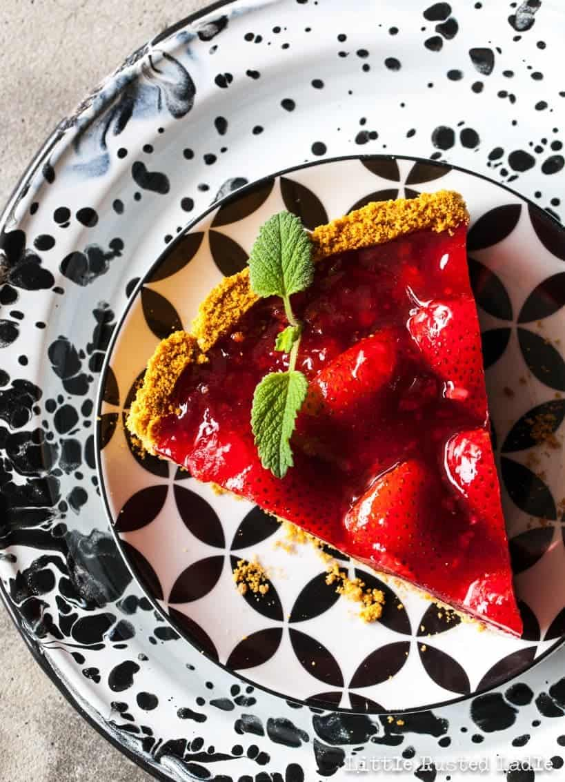 A piece of bright red strawberry pie on patterned black and white dishware.