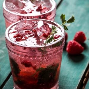 Two garnished glasses of homemade raspberry soda on green wood surface