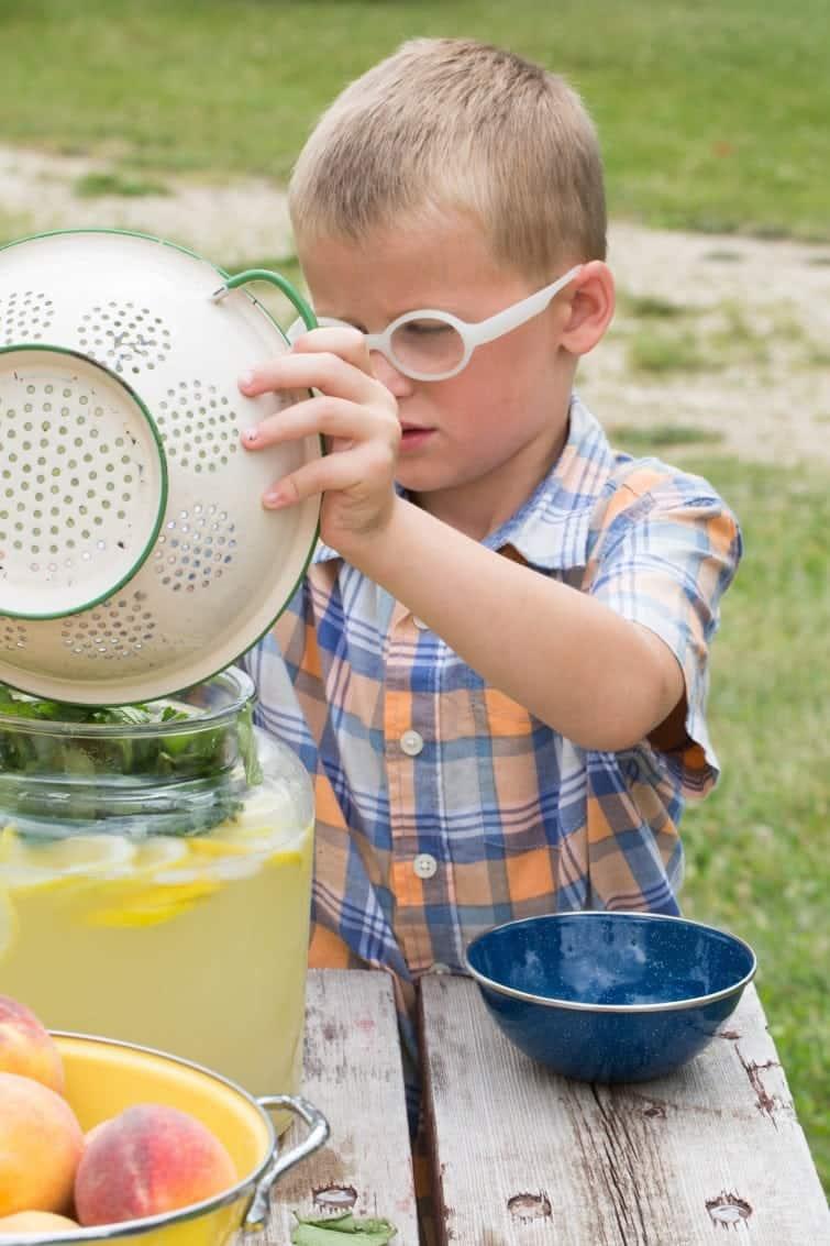boy making lemonade at picnic table