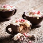 A chocolate teacup cracked open to reveal hot cocoa mix with peppermint pieces