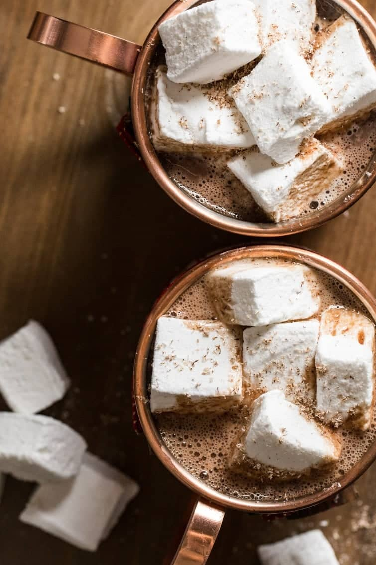 Two copper mugs with hot cocoa topped with huge homemade marshmallow squares