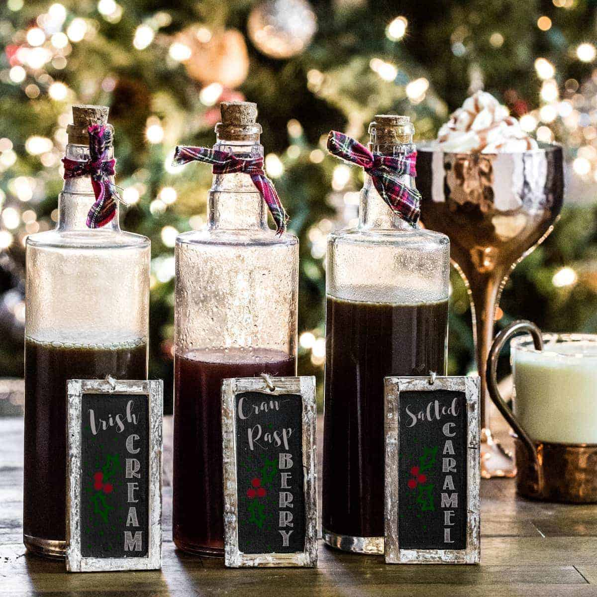 Three glass bottles of homemade syrup with chalkboard signs in front of a Christmas tree