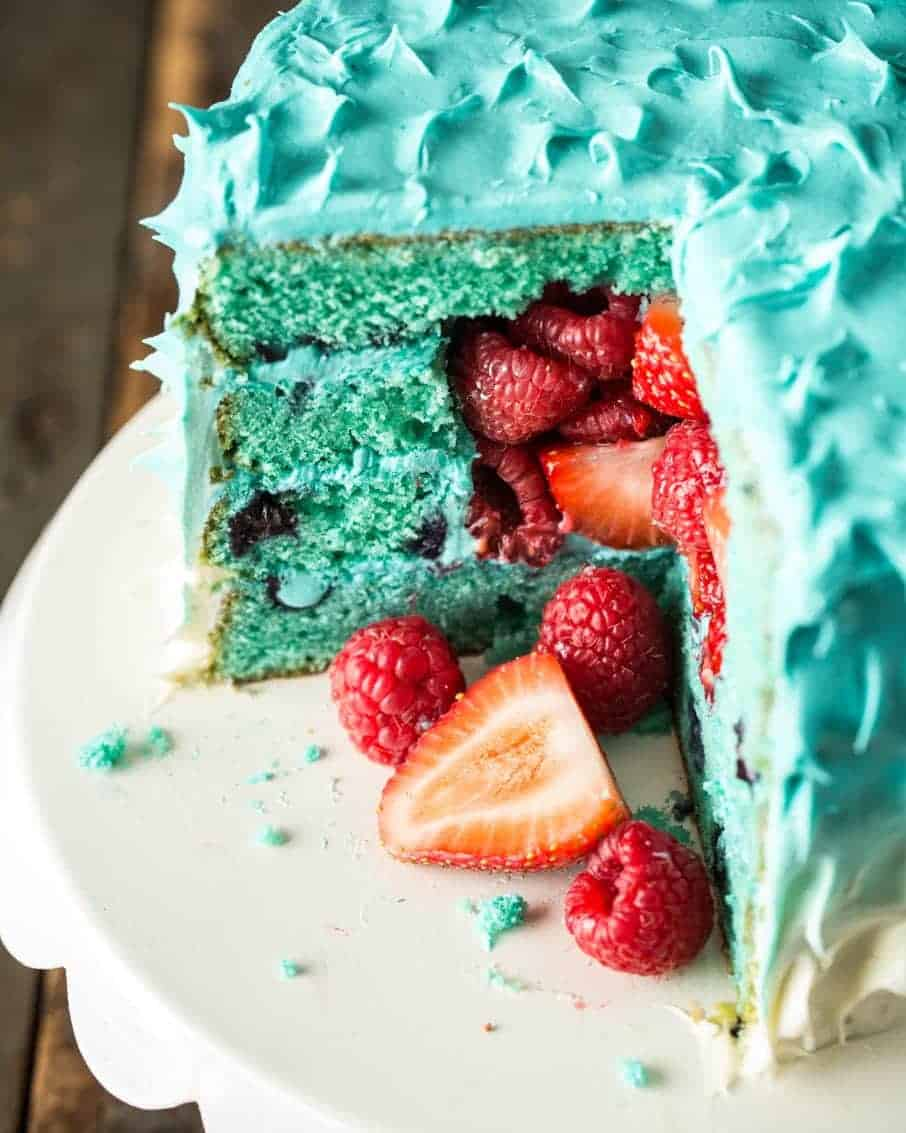 A light blue ombre cake with a quarter cut out. Fresh strawberries tumble out.