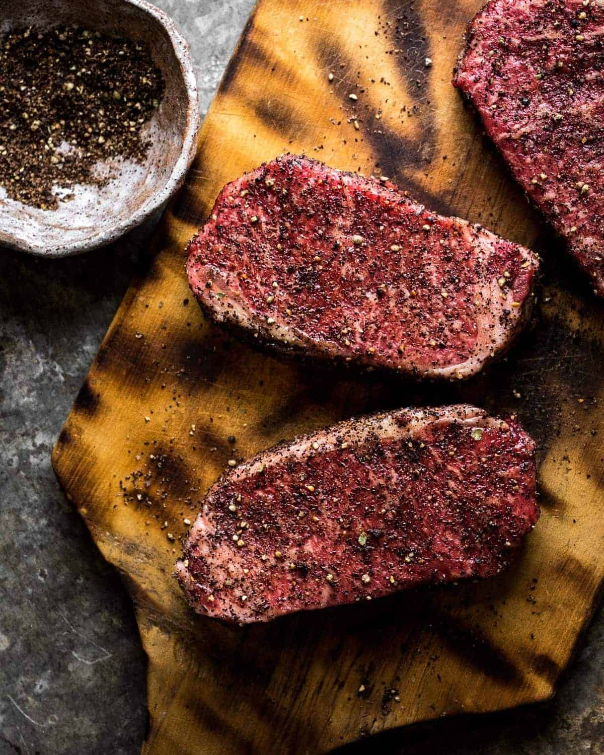 strip steaks covered in coffee seasoning mix resting on a vintage wooden cutting board.