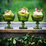 Three vintage green glass goblets on a rustic outdoor surface with light pear and rhubarb salad
