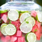 Large beverage container with fresh limes and watermelon pieces floating in limeade