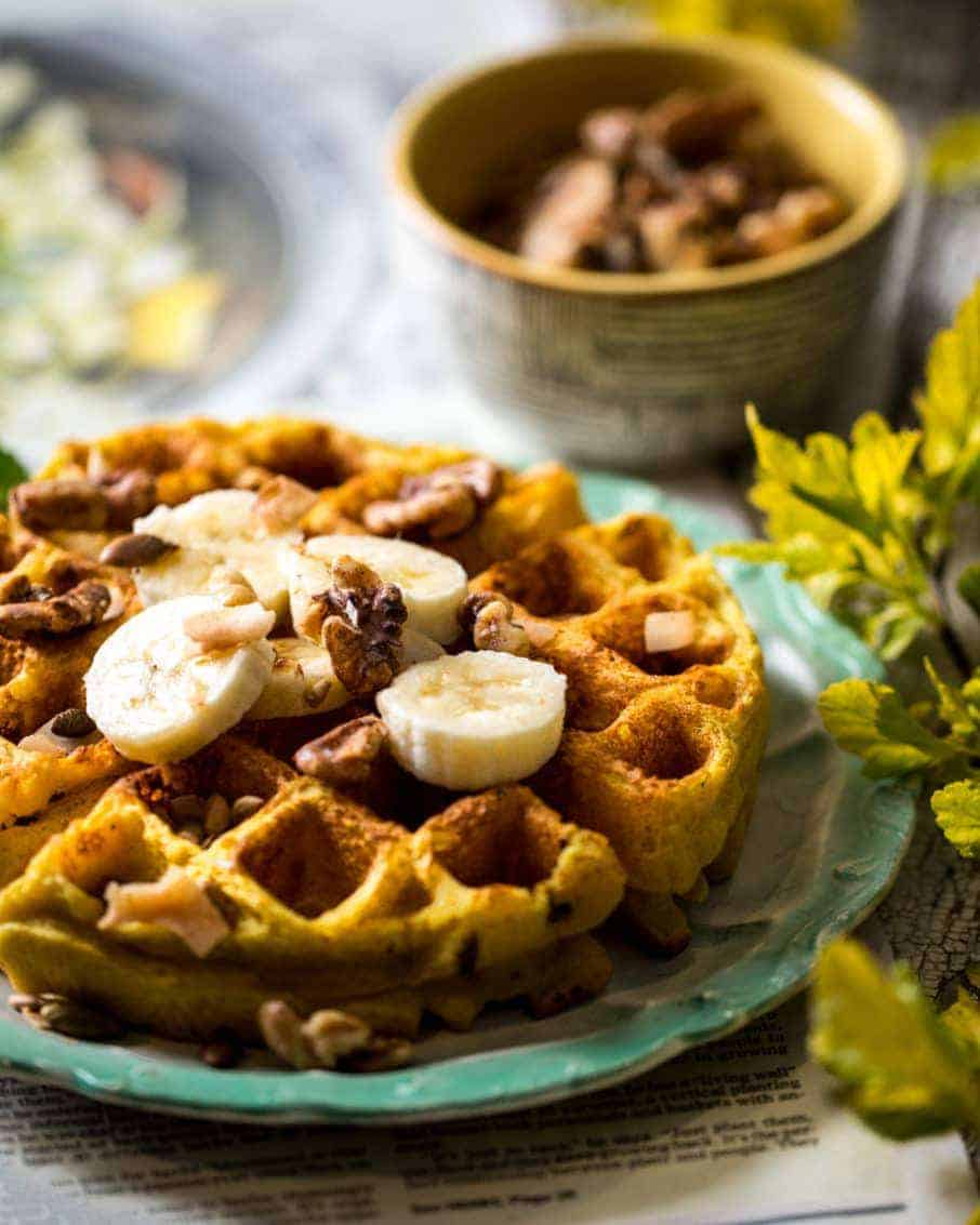 3/4 shot of big fluffy waffle with sliced bananas, chopped nuts, and chocolate