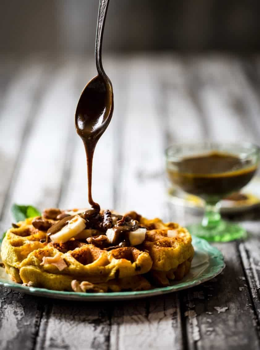A spoon dripping chocolate onto a turmeric waffle with sliced bananas and nuts
