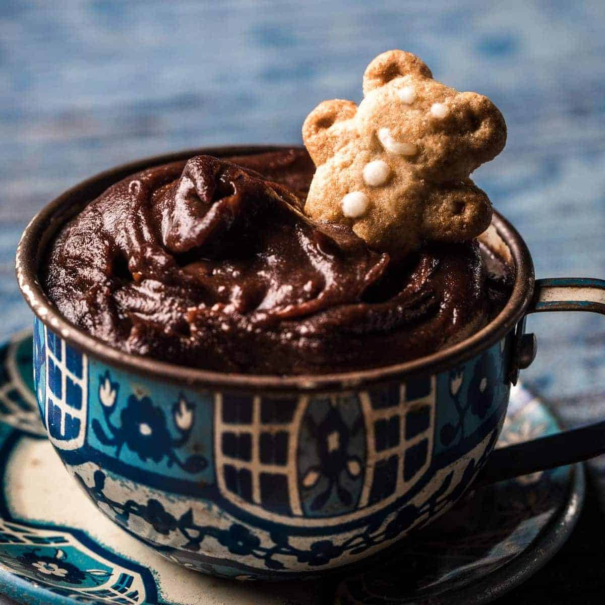 Teacup of chocolate dessert hummus with teddy bear cookies for dipping