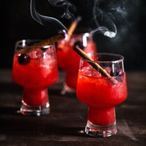 Trio of bright red Smoked apple old fashioneds with smoking cinnamon sticks