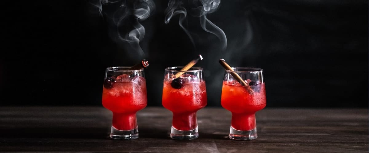 Three glasses of Candy Apple Old Fashioned with smoking cinnamon sticks. .
