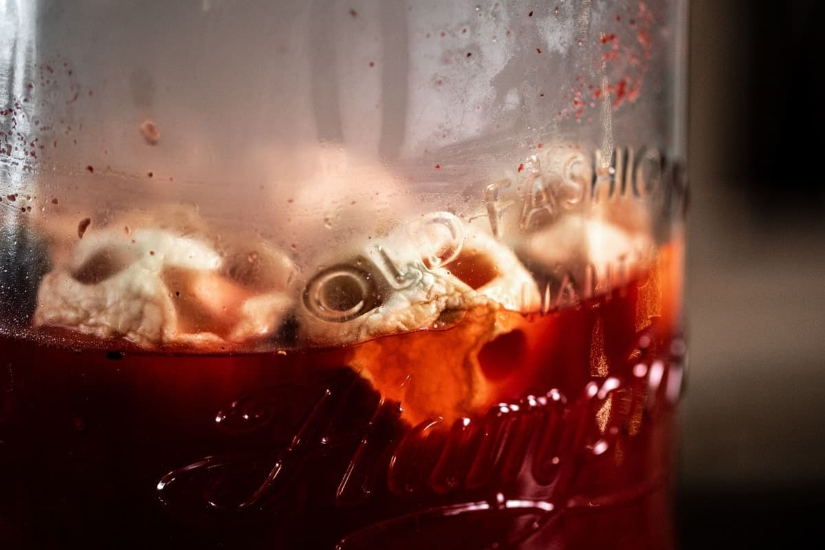 Apple Skulls floating in Old Fashioned from the side
