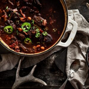 overhead shot of croc of venison chili with corn bread and antlers