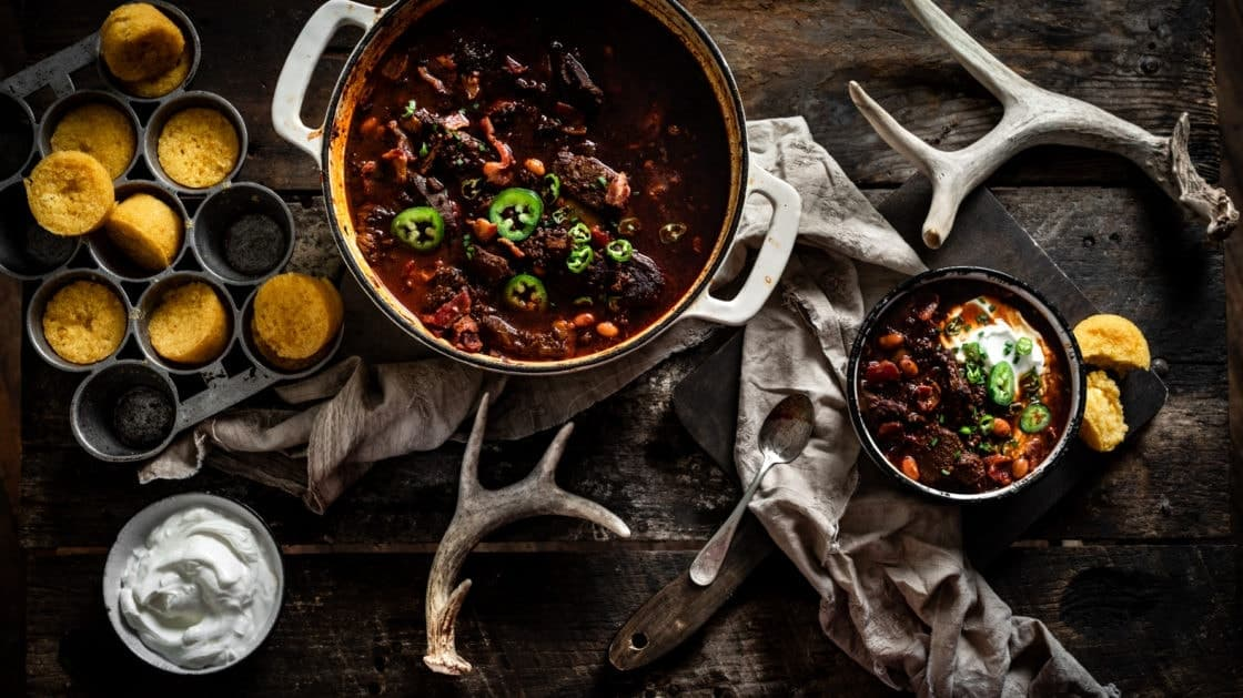 Overhead shot of rustic table setting with pot of venison chili, corn bread, and antlers