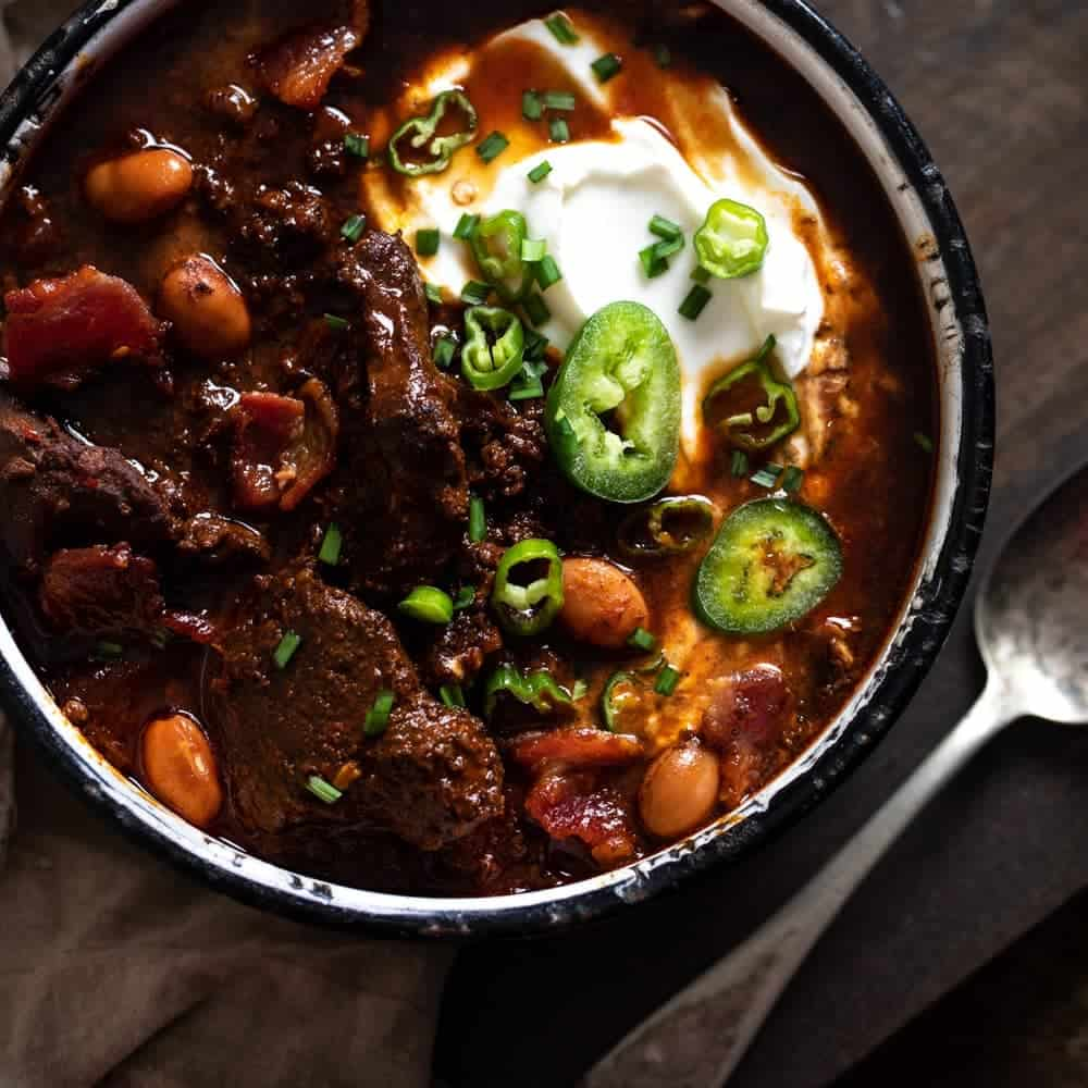 Overhead photo of venison chili with jalapenos and sour cream