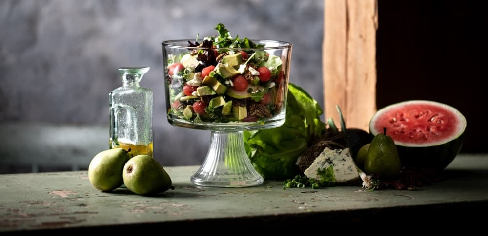 Bright salad in a glass serving bowl surrounded by ingredients.