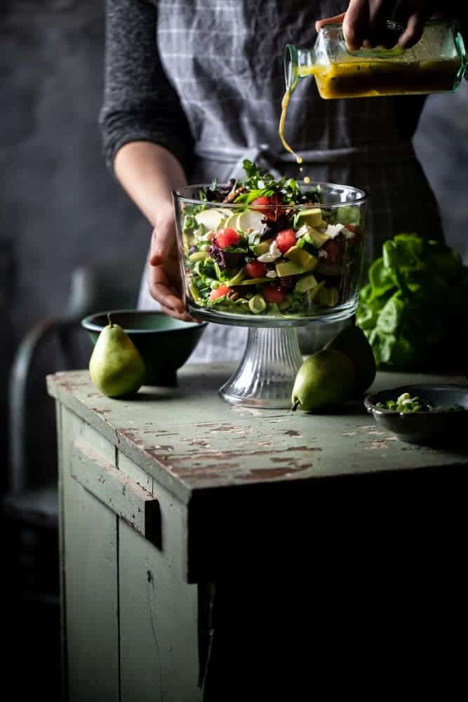Pouring dressing into a glass serving bowl of melon avocado salad with a dark background.