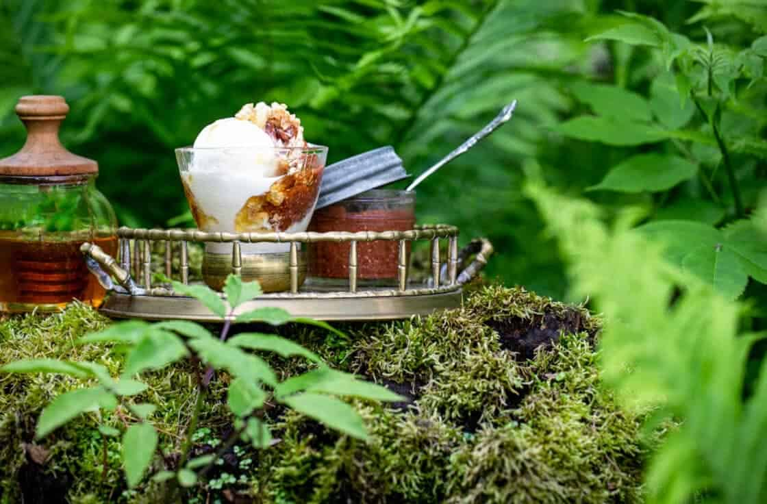 Gold tray with a frozen yogurt sundae, jar of strawberry rhubarb chia jam, and honey pot on a verdant stump.