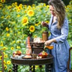 Jena Carlin standing by a table set up of sunflower dishes in a sunflower field