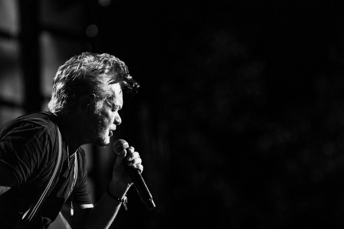 John Mellencamp singing into a microphone at Farm Aid with his profile dramatically back lit