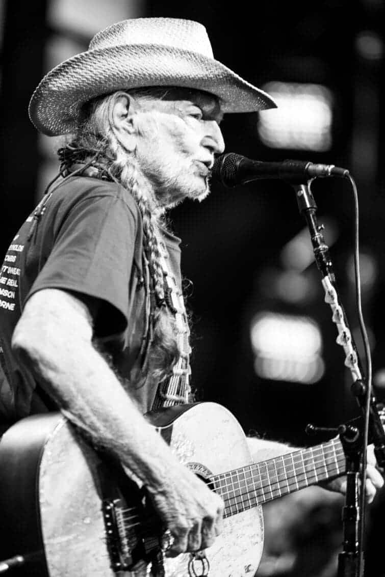 Willie Nelson playing the guitar at a microphone at Farm Aid