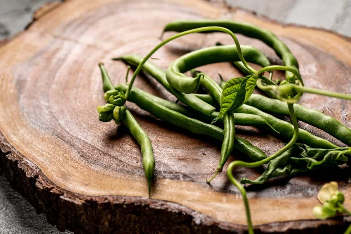 fresh green beans on a wood slice