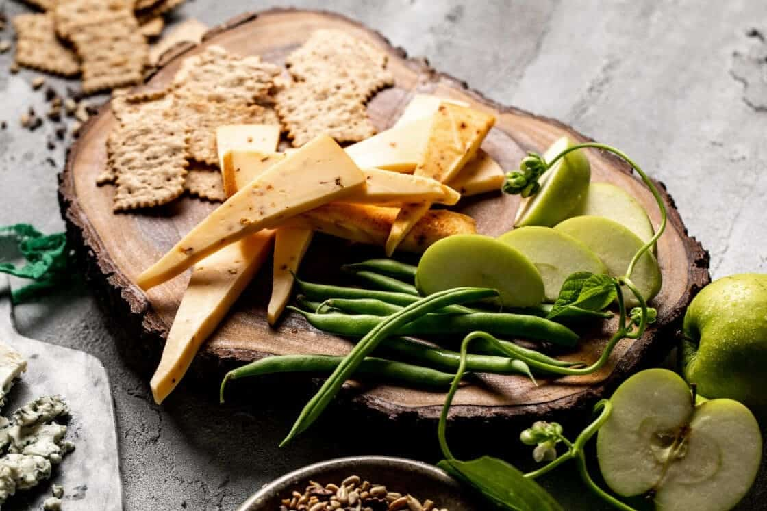 Cheese board on a log cutting with crackers and vegetables