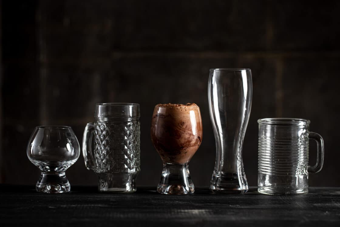 A line of fun glassware with only the center one full. Seeing lighting techniques in commercial drink photography