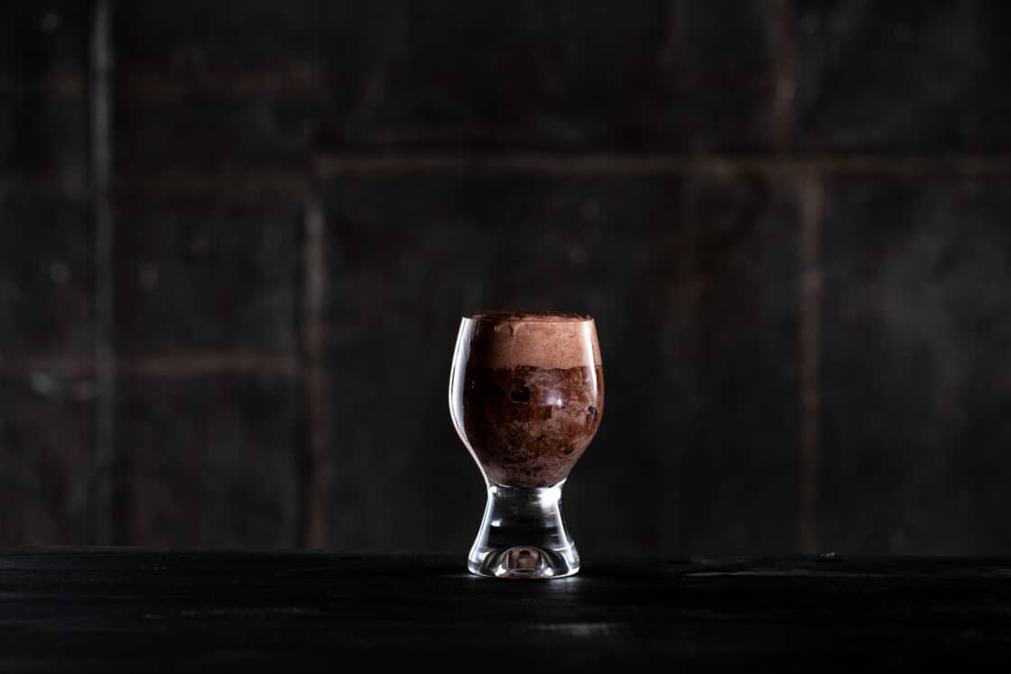 a single glass with a wide base filled with a brown beer float. Dark background with dramatic lighting.