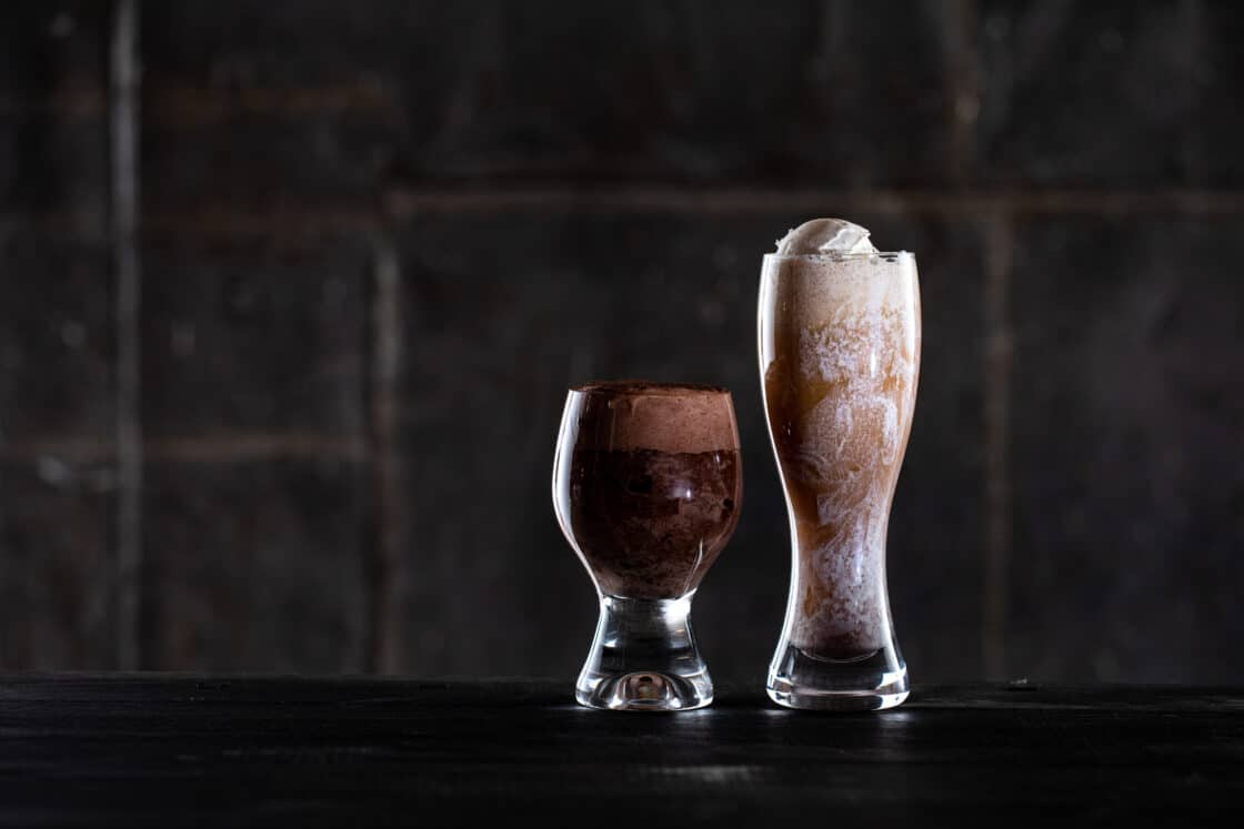Two fun glasses with beer floats in them. Showing how lighting of first glass blocks the second.