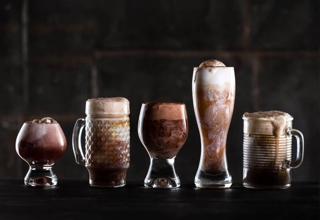 A line of fun glassware filled with creamy beer floats against a dark background