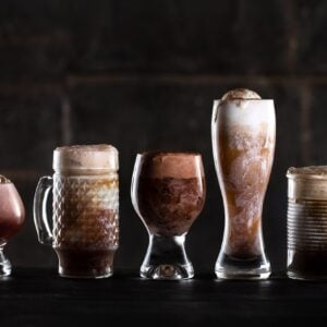 professional drink photo with A line of fun glassware filled with creamy beer floats against a dark background
