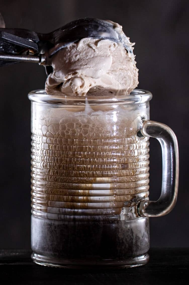 Hand scooping ice cream into a frosty mug of beer.