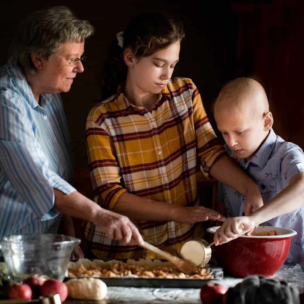 Grandmother and grandchildren working together to make an apple dessert