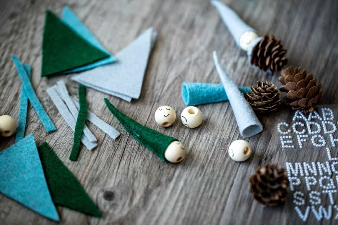 pine cones, felt, and wooden beads on a light gray wood surface. DIY Secret Santa supplies