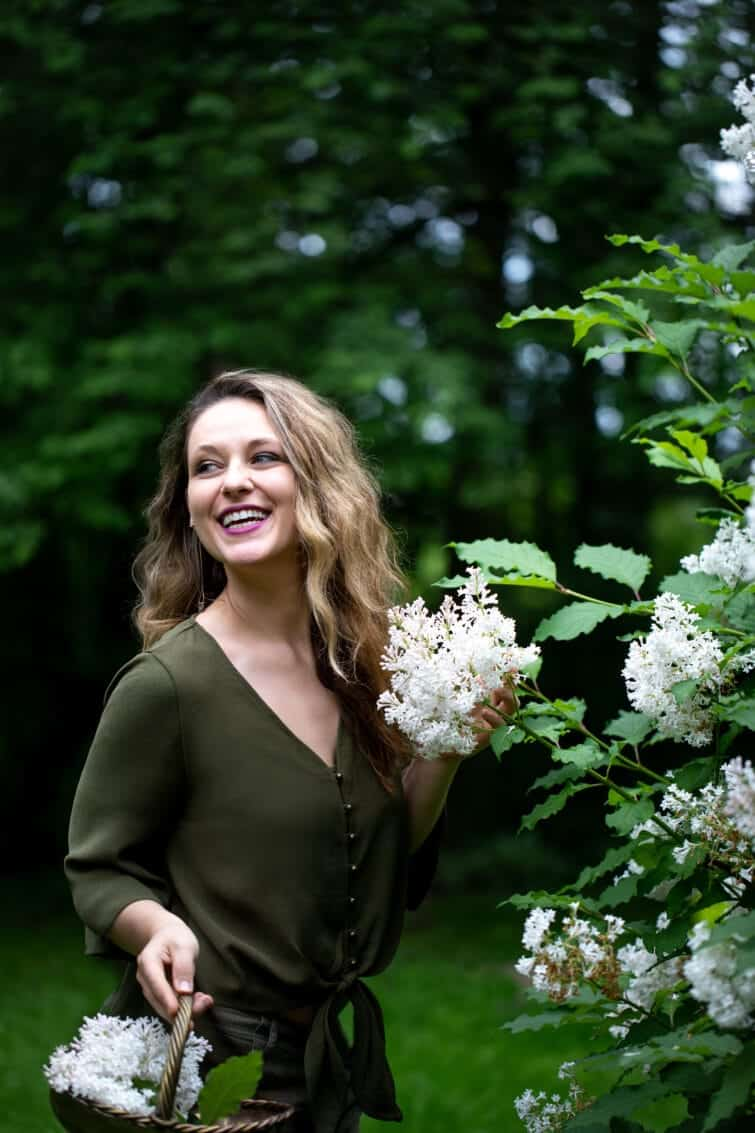 Woman picking white lilacs smiling with a brass basket
