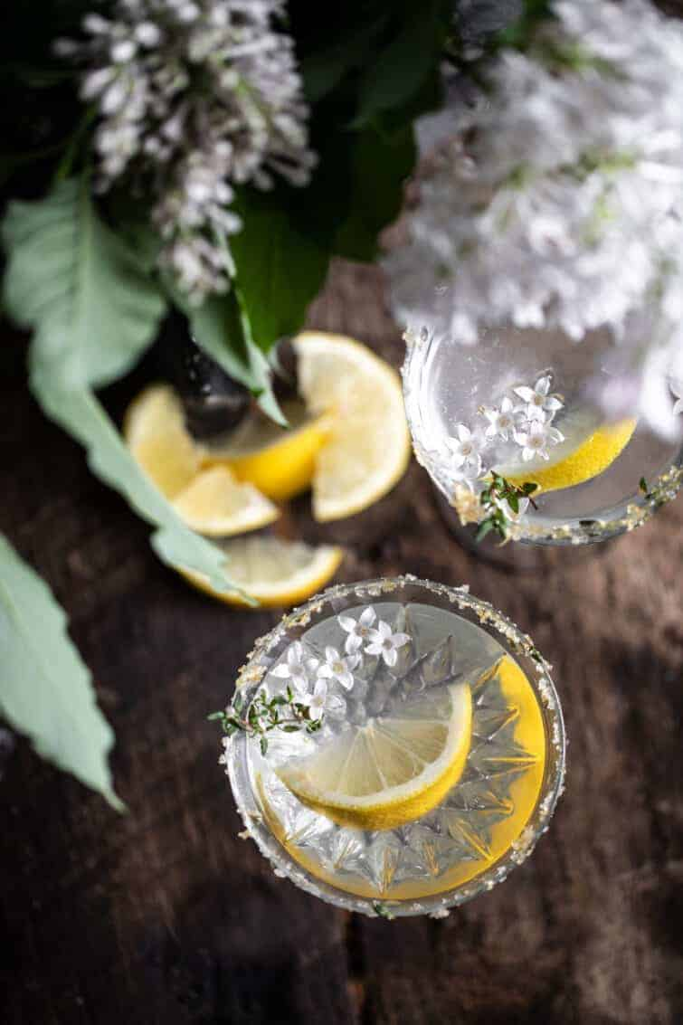 beautiful overhead garnished drink photography lemon drop martini in rustic wood setting with thyme lemon zest and lilac on the rim of the class recipe bordered by a bunch of white lilacs