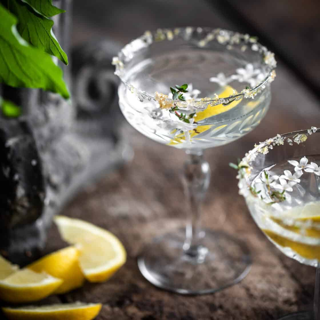 Lemon drop martini in rustic setting with thyme lemon zest and lilac on the rim of the glass 3/4 view of garnished drink photography